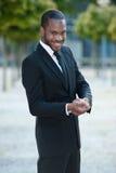 Junger schwarzer Mann, der draußen in einer Klage lächelt Lizenzfreie Stockfotos
