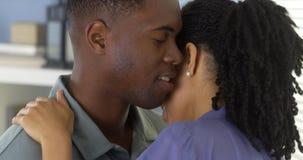 Junger schwarzer Mann, der Freundin hält und in ihr Ohr flüstert stockfoto