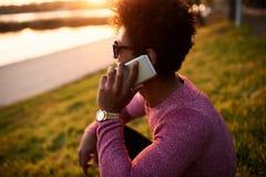 Junger schwarzer Mann, der am intelligenten Telefon lächelt und spricht Lizenzfreies Stockfoto