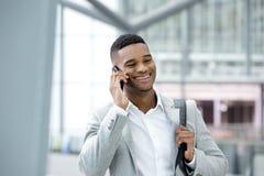 Junger schwarzer Mann, der mit Mobiltelefon lächelt Lizenzfreie Stockbilder