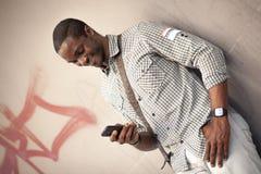 Junger schwarzer Mann, der Mitteilungen an seinem intelligenten Telefon überprüft lizenzfreies stockfoto