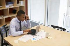 Junger schwarzer Mann, der Smartphone in einem Sitzungssaal, erhöhte Ansicht verwendet lizenzfreie stockfotografie