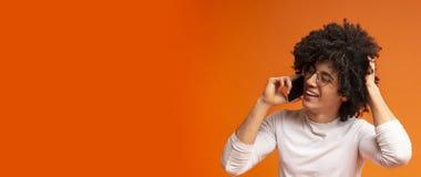 Junger schwarzer Mann, der am Telefon, schauend schüchtern und spricht verlegen lizenzfreies stockbild