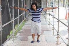 Junger schwarzer Mann, der unter Baugerüst aufwirft Lizenzfreie Stockfotos