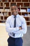 Junger schwarzer Mann, der zur Kamera in einem Sitzungssaal, vertikal lächelt stockbilder