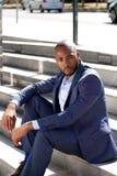 Junger schwarzer Mann im Anzug, der draußen auf Schritten sitzt Stockfoto