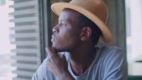 Junger schwarzer Mann sitzt in einem modischen Café stock footage
