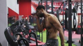 Junger schwarzer Mann während der Übung auf elliptischem Trainer stock footage