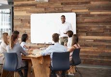Junger schwarzer Mann am whiteboard, das eine Geschäftsdarstellung gibt stockfotografie