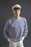 Junger Seemanmann mit weißem Seemannhut Stockbild
