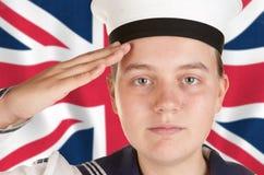 Junger Seemann, der vor Union Jack begrüßt Lizenzfreie Stockfotos