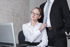 Junger Sekretär, der Chef durch Bindung im Büro zieht Stockfotos