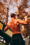 Junger sexy Athletenmann mit dem nackten Torso, der ZugUPS im Park tut lizenzfreies stockbild