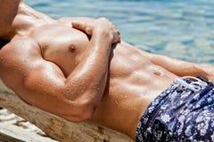 Junger sexy nasser Kerl, der auf dem Strand liegt Stockbilder