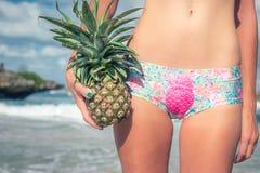 Junger sexy tropischer Frauenkörperabschluß oben mit Ananas Eignungskörperdame auf dem Strand Bali-Insel Stockfoto