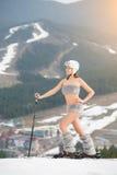 Junger sexy weiblicher Skifahrer wirft auf die Oberseite der Steigung mit Skis auf Tragende Stiefel, Sturzhelm und Sonnenbrille Lizenzfreies Stockbild