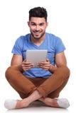 Junger Sitzmann mit dem Tablettenauflagenlächeln Lizenzfreie Stockbilder