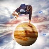 Junger Skateboardfahrer, der über den Jupiter-Planeten springt Lizenzfreie Stockfotos
