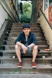 Junger Skateboardfahrermann, der draußen auf seinem Skateboard lächelt und stillsteht Graue Treppe und Graffiti auf den Wänden au stockbild
