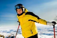 Junger Skifahrer, der auf Bergen steht Stockfotografie