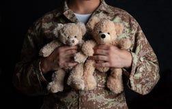 Junger Soldat, der einen Teddybären steht auf schwarzem Hintergrund hält lizenzfreies stockbild