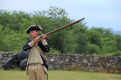 Junger Soldat kleidete in der Zeitraumkleidung an und zeigte Musketenzündung, Fort Ticonderoga, New York, 2014 Lizenzfreies Stockbild
