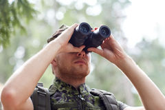 Junger Soldat oder Jäger mit binokularem im Wald Lizenzfreie Stockbilder