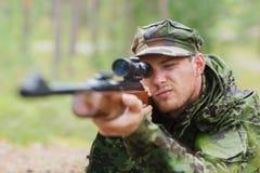 Junger Soldat oder Jäger mit Gewehr im Wald Stockbilder