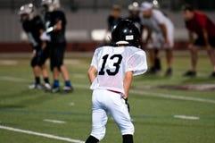 Junger Spieler des amerikanischen Fußballs in Position Lizenzfreie Stockbilder