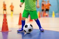 Junger Spieler des Hallenfußballs mit einem Fußball in einer Sporthalle Spieler in der grünen Uniform Basketball mit Metallflügel Lizenzfreies Stockfoto