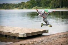 Junger spielerischer kaukasischer Junge, der in das mitten in der Luft macht einen Sprung von einer Anlegestelle zum Strand läuft lizenzfreie stockfotos