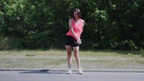 Junger sportiver Mädchentanzenrucksack-Kindertanz im Park Attraktives Mädchen in den Kopfhörern, die Glasschlackentanz im Park du stock video footage
