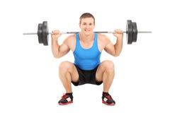 Junger Sportler, der ein Schwergewicht anhebt Stockfotos