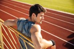 Junger Sportler mit der Flasche Wasser lehnend auf dem Geländer stockbild