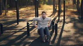 Junger Sportler tut Sport draußen im Parksportboden, der am Arm und Beinmuskeln und -aBS unter Verwendung der Metallstangen arbei stock footage