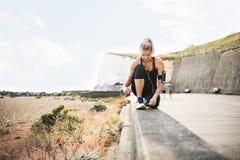 Junger sportlicher Frauenläufer mit den Kopfhörern, die Spitzee durch den Strand binden stockbilder