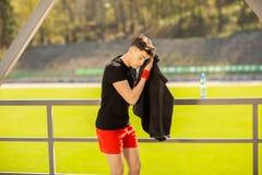 Junger sportlicher Mann, der drau?en seinen Schwei? mit einem Tuch nach Trainingssport?bungen liegt und abwischt stockfotografie