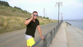 Junger sportlicher Mann in der Sonnenbrille sprechend am Telefon auf der Seeseite stock footage