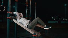 Junger sportlicher Mann hebt die Beine an, die auf Sportausrüstung im Nachtpark liegen stock video