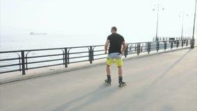 Junger sportlicher Mann lernt zum Rollschuh und zum Sprung auf Ufergegend stock video