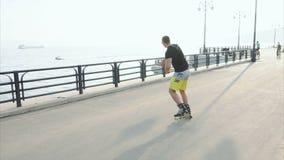 Junger sportlicher Mann lernt zum Rollschuh und zum Sprung auf Ufergegend stock footage