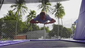 Junger sportlicher Mann macht die extremen Tricks, die auf Trampoline springen stock video