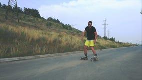 Junger sportlicher Mann mit Inline-Rochen reiten in Sommerufergegend stock video