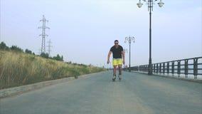 Junger sportlicher Mann mit Inline-Rochen reiten und springen in Sommerufergegend stock footage