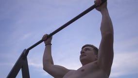 Junger sportlicher nackter Kerl zieht sich oben auf der horizontalen Stange, die auf dem Hintergrund des blauen Glättungshimmels  stock video footage