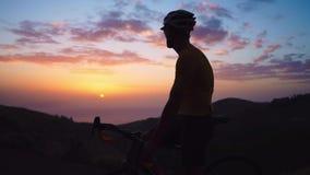 Junger Sportmann, der auf einem Fahrrad auf eine Gebirgsoberseite in einer gelben T-Shirt Sturzhelm- und Sportausrüstung betracht stock video