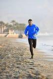 Junger Sportmann, der in Eignungstraining auf dem Strand entlang dem Seefrühen Morgen läuft Stockfotos