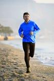 Junger Sportmann, der in Eignungstraining auf dem Strand entlang dem Seefrühen Morgen läuft Stockbild