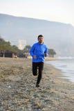 Junger Sportmann, der in Eignungstraining auf dem Strand entlang dem Seefrühen Morgen läuft Stockfotografie