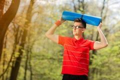 Junger Sportmann im roten T-Shirt, das in einem Fr?hlingspark mit einer blauen Yogamatte aufwirft Er h?lt eine Yogamatte ?ber sei lizenzfreies stockbild